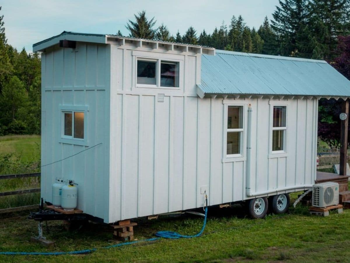 Side of tiny home showing white siding teal roof and four windows