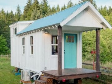 White tiny house with teal roof on grass with porch