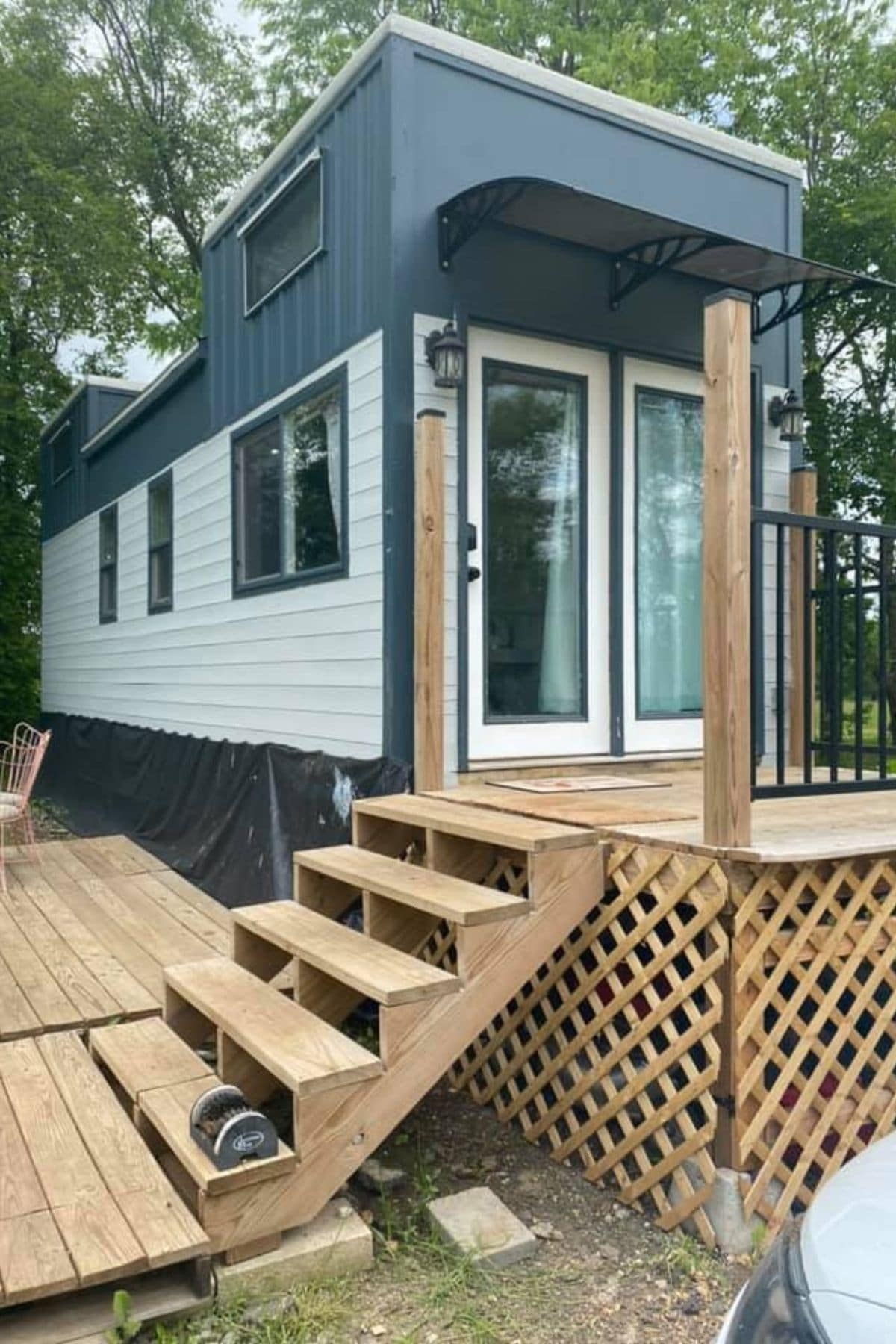 Gray and white tiny home with glass doors on end and wood front porch