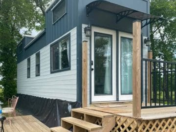 Tiny house with dual lofts and gray and white siding