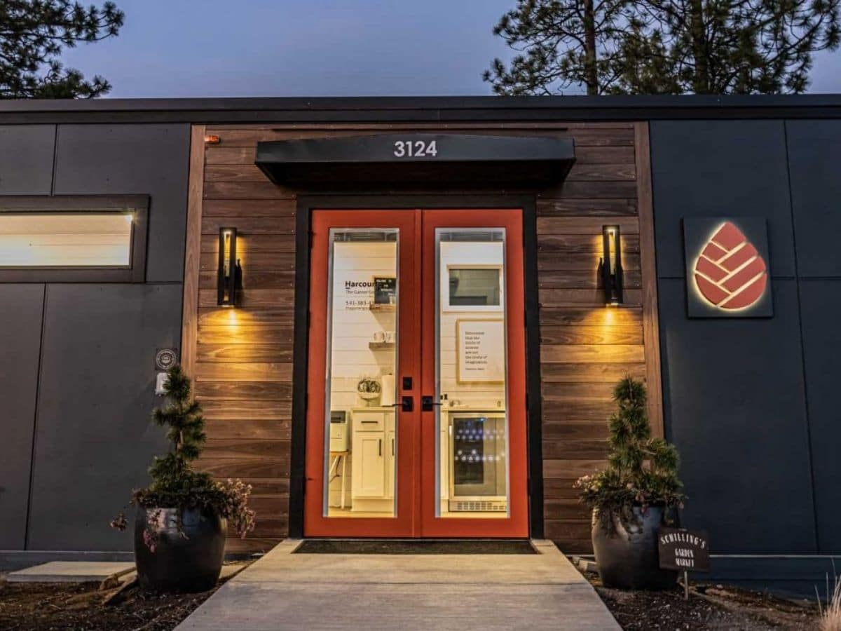 Front doors to tiny house lit up after dark with orange trim