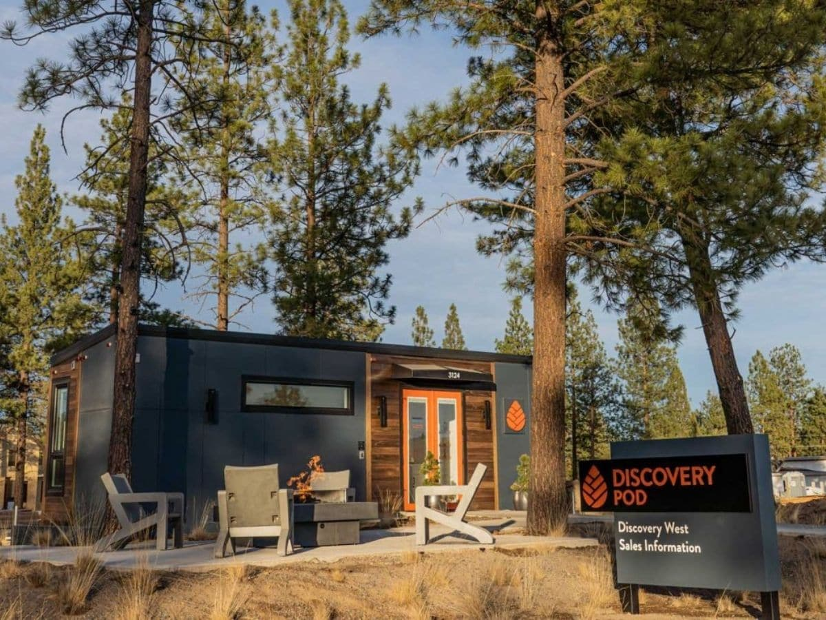 Blue gray tiny house in treeline with business sign out front