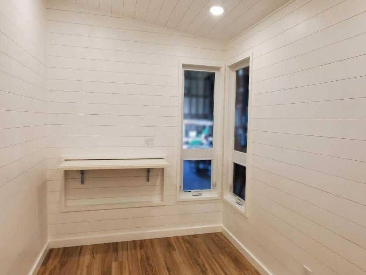 White walls with white shelf on wall by corner windows