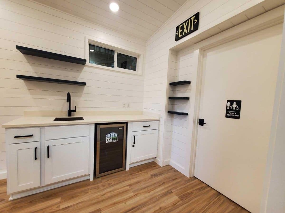 White walls and cabinets in tiny home with wet bar against wall