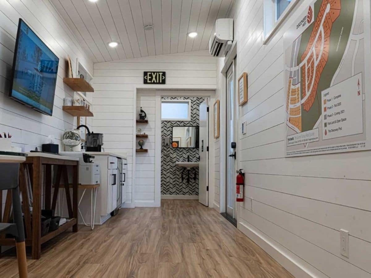 White shiplap walls and light wood floors with open door to bathroom in background
