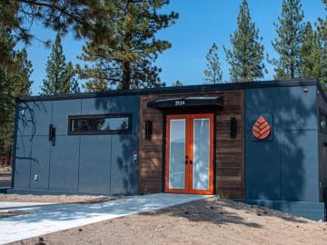 Blue gray tiny home with orange trim on hill with concrete walkway