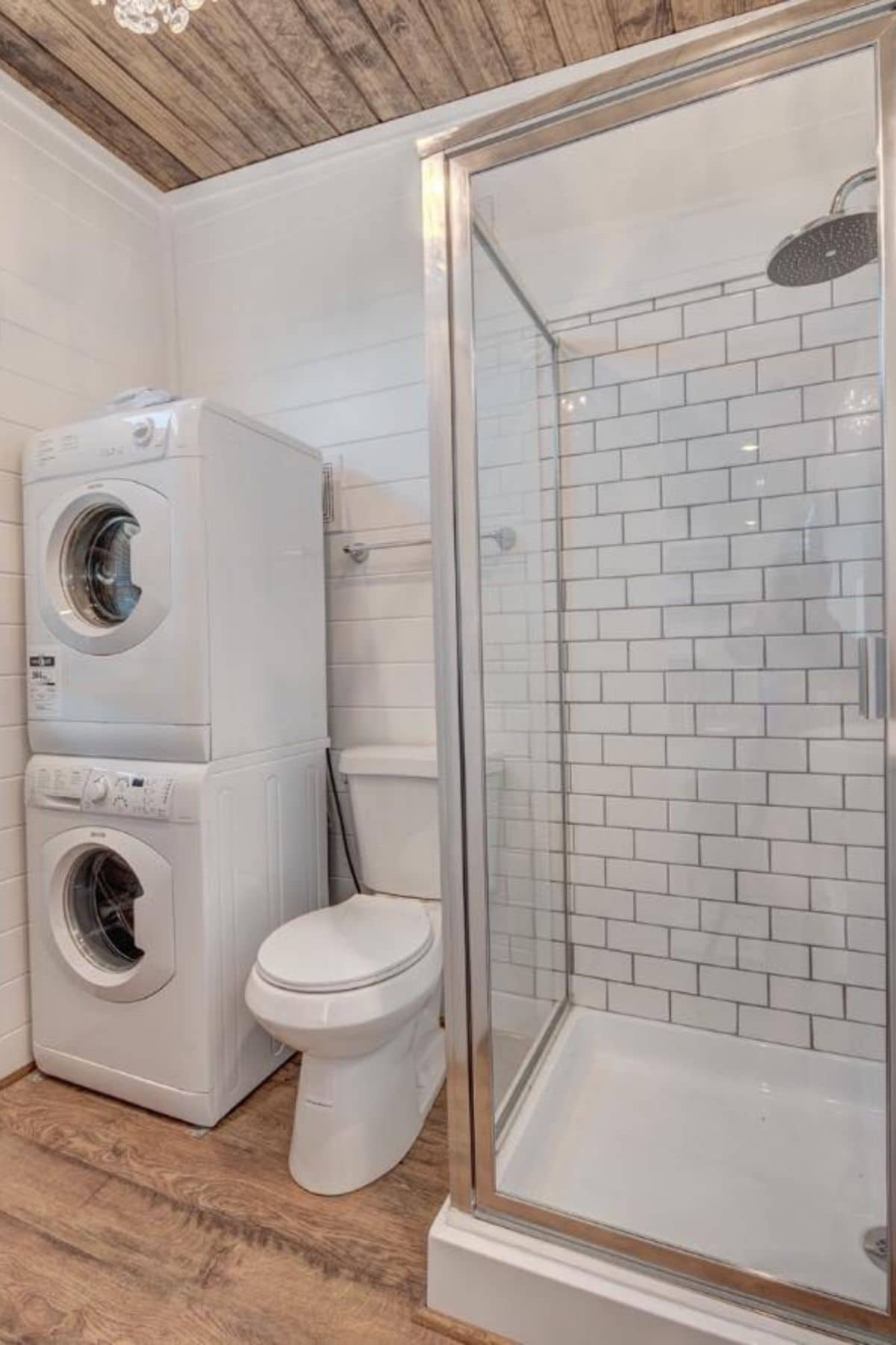 Bathroom with stacking washer and dryer and shower with toilet between the two