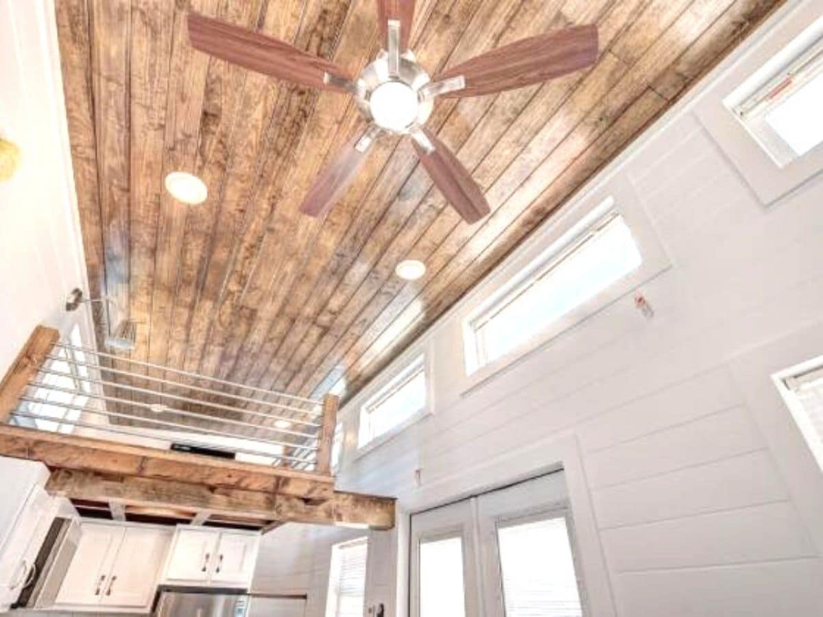 Wood ceiling with white walls and ceiling fan in tiny home