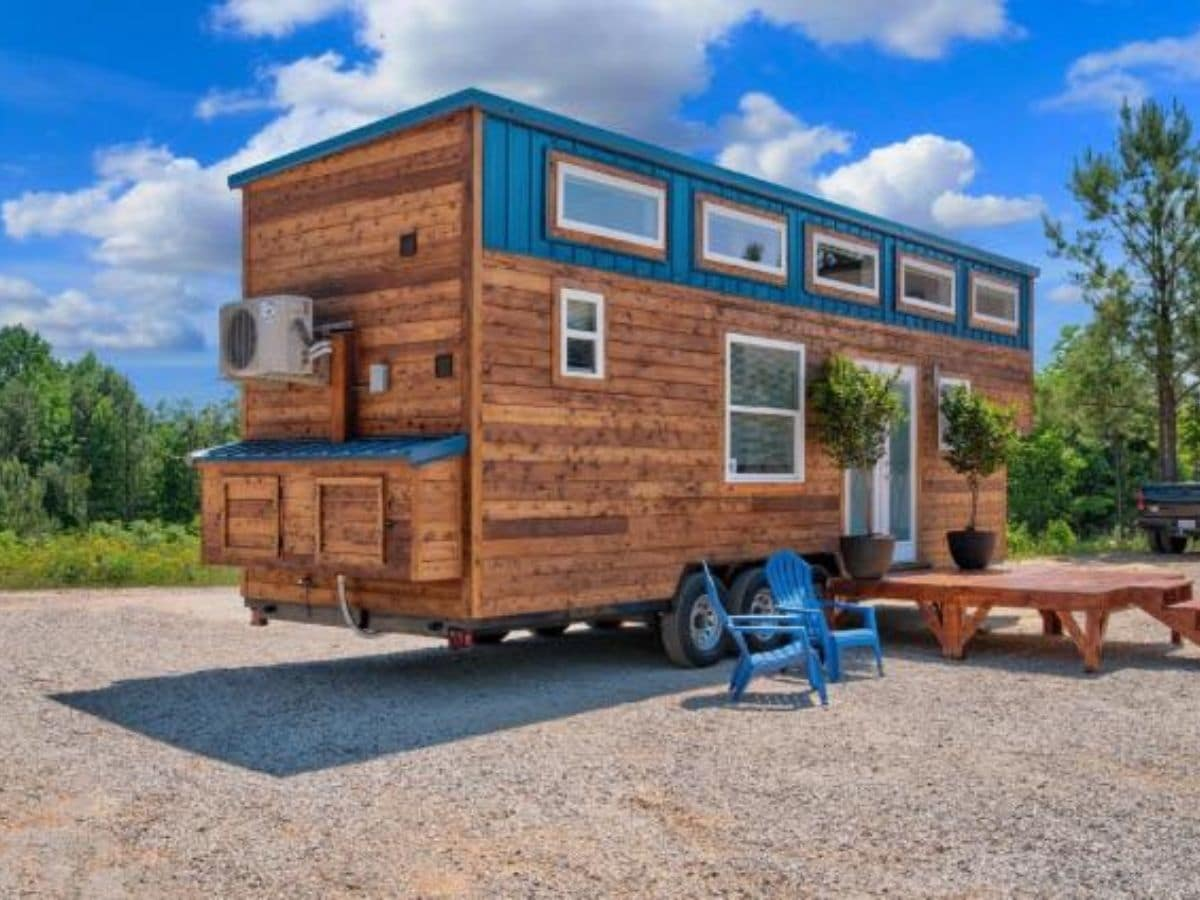 Tiny home on lot with wooden porch beside teal deck chairs