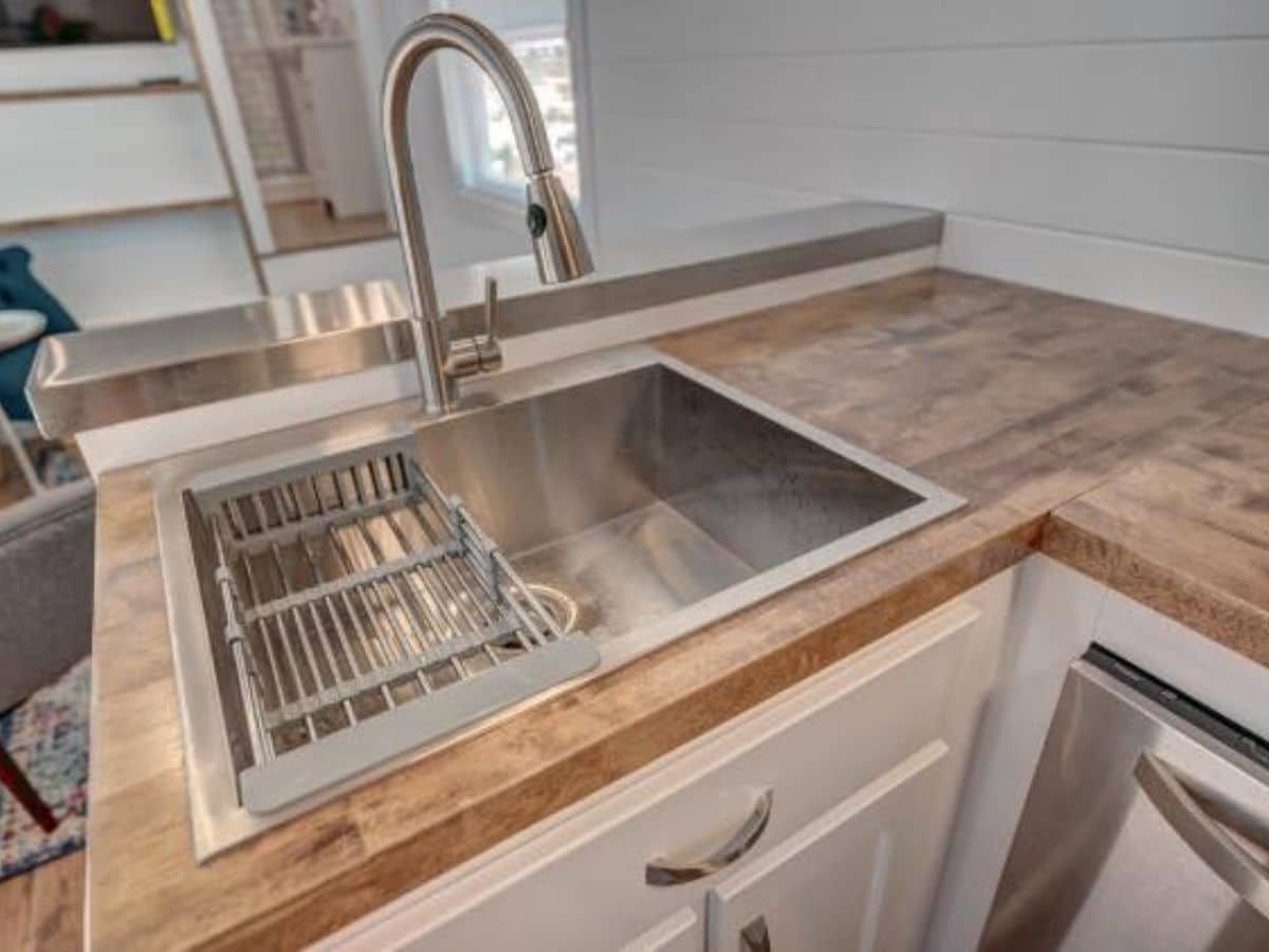 Deep stainless steel sink with dish drainer and tall faucet