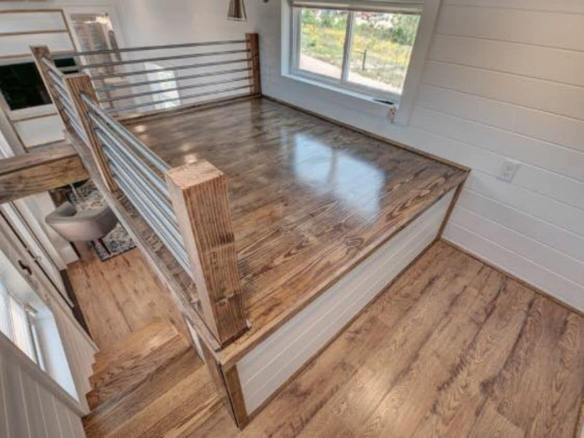 Wood flooring in loft with gray railings and platform