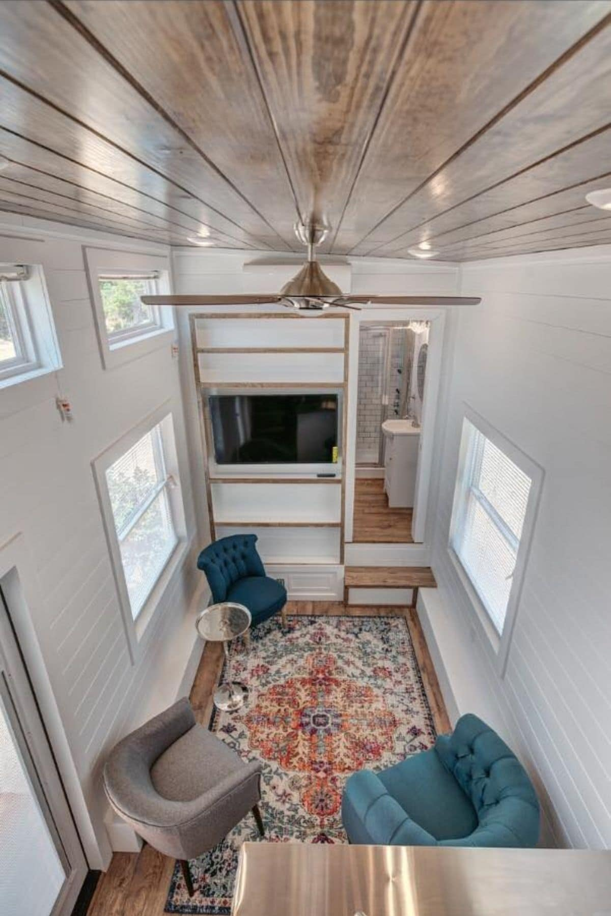 View from loft into main tiny home floor showcaseing white walls