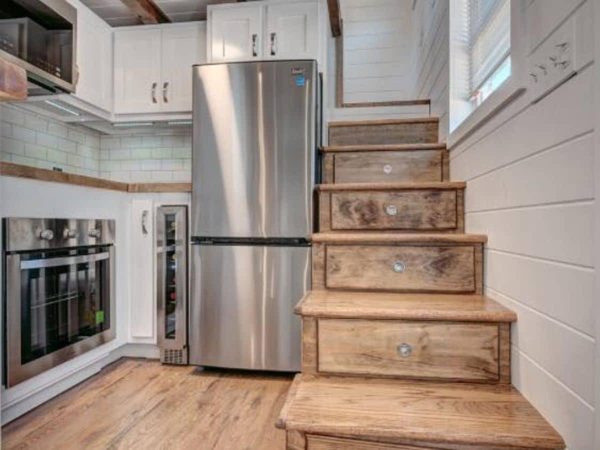 Wood stairs beside stainless steel refrigerator