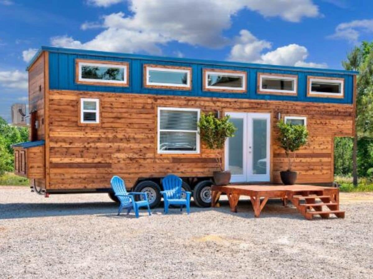 Wood siding on tiny house with white trim and teal accents