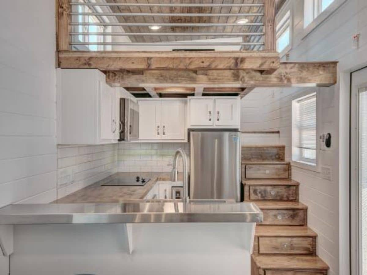 View into kitchen with white counters and stainless steel appliances and light wood stairs