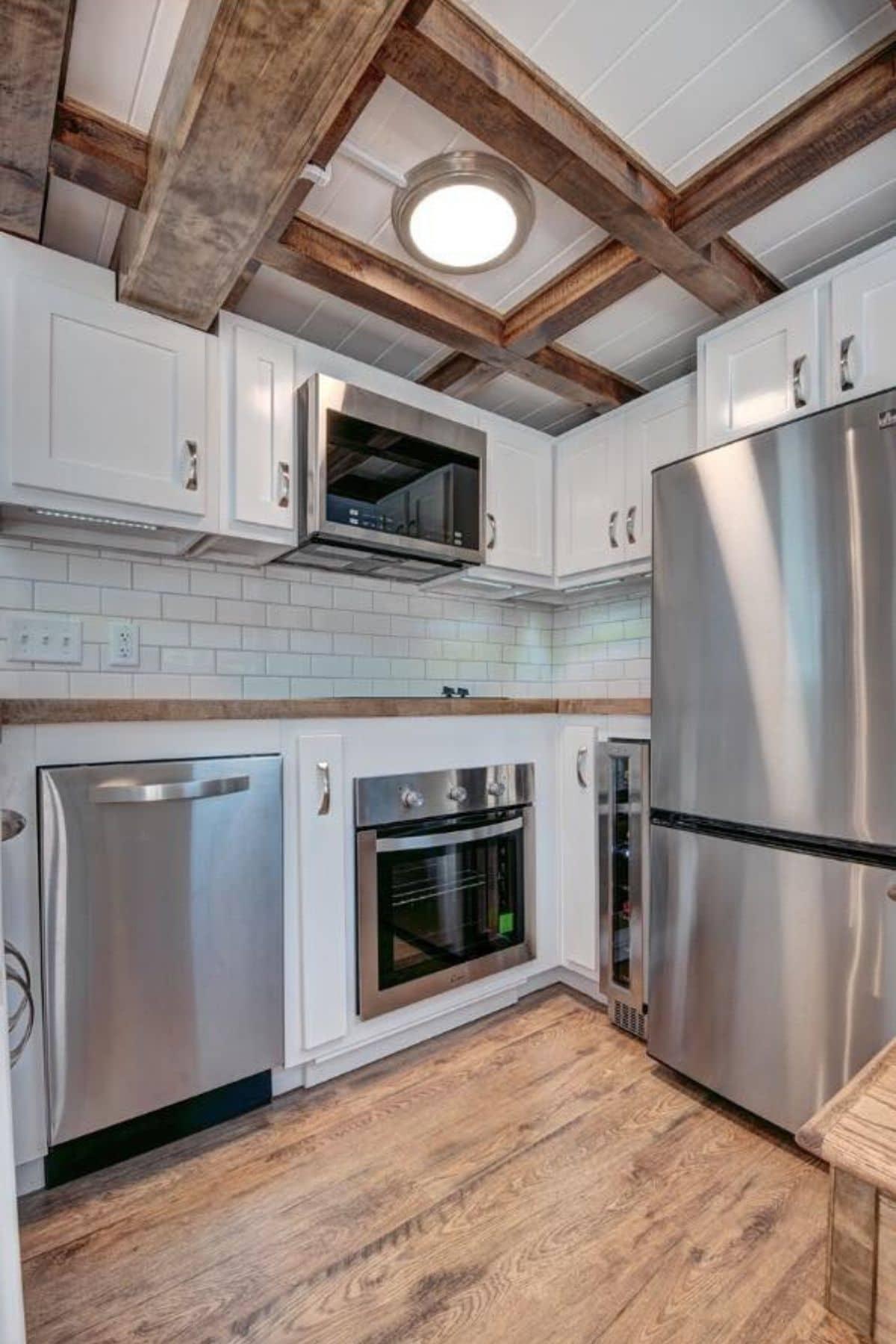 Kitchen with white cabinets dishwasher oven wine fridge and refrigerator