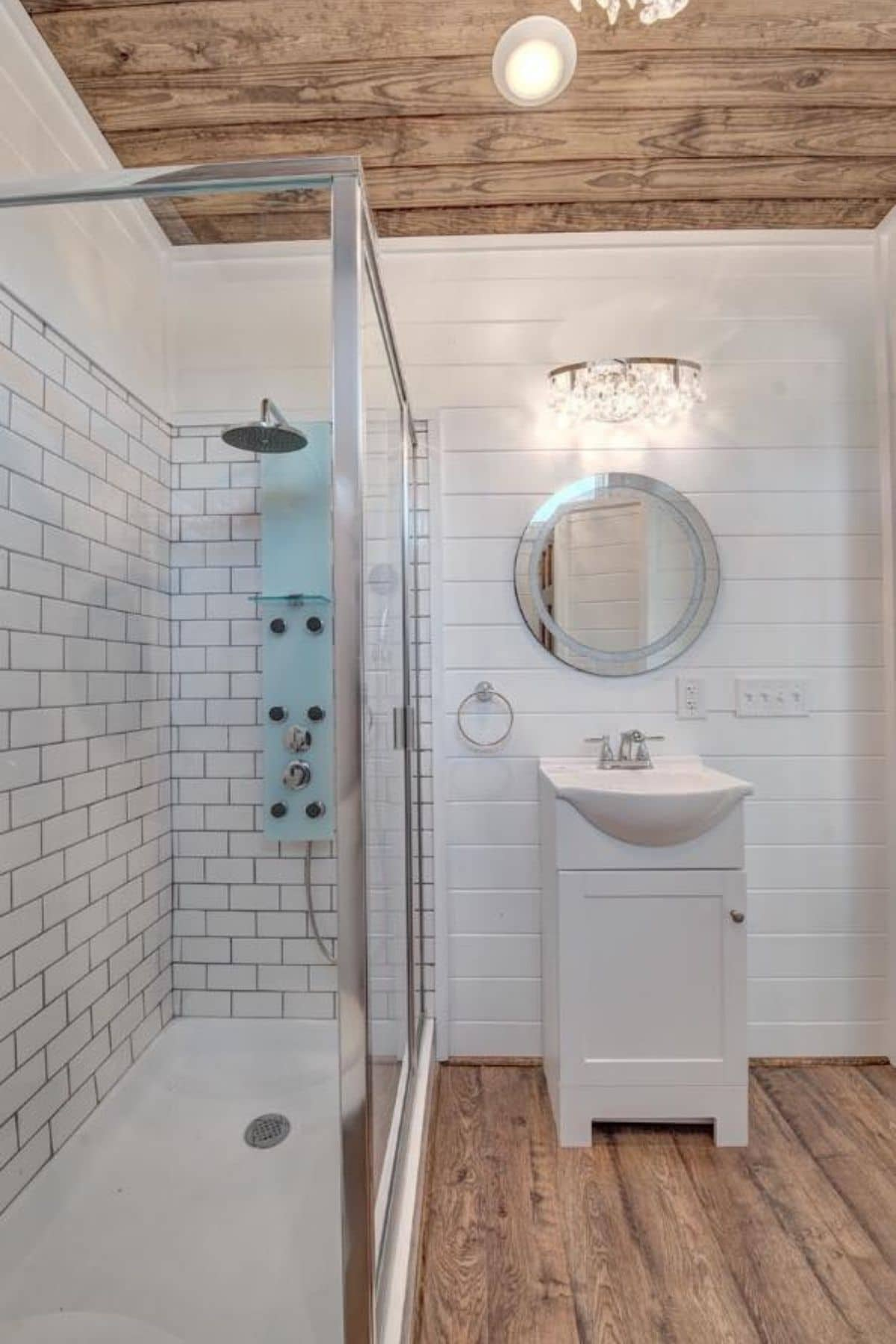 Tiled shower with glass door beside small white vanity with round mirror