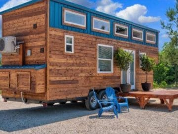 Tiny home with wood siding with teal accent and white trim