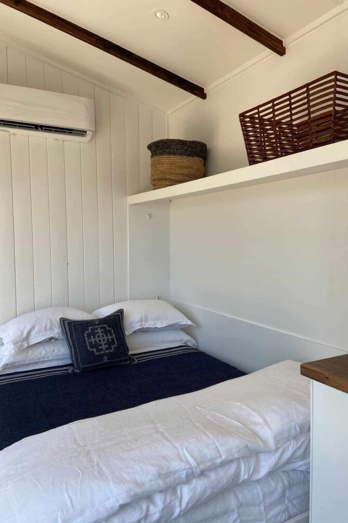 White murphy bed against white shiplap wall with blue blanket