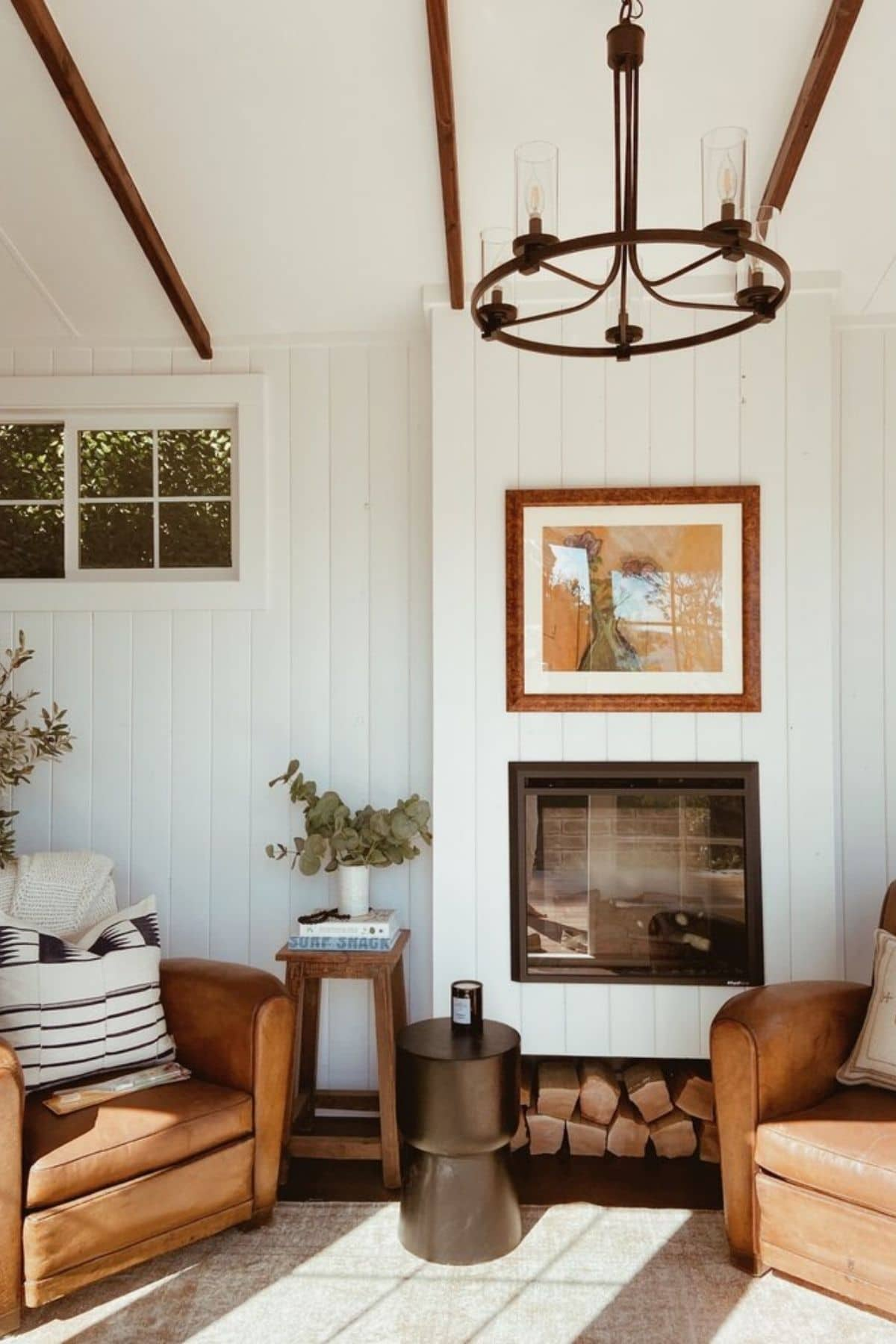 White shiplap wall with fireplace inset next to brown chairs and rustic light
