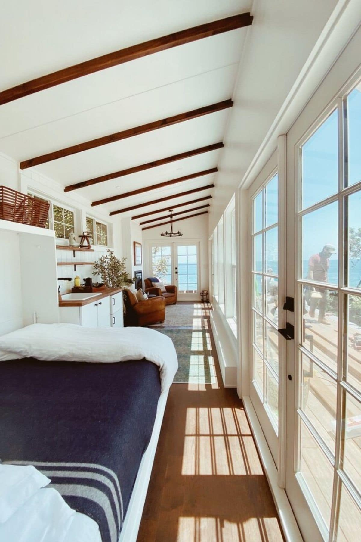 View down middle of tiny home with windows on right and bed on left