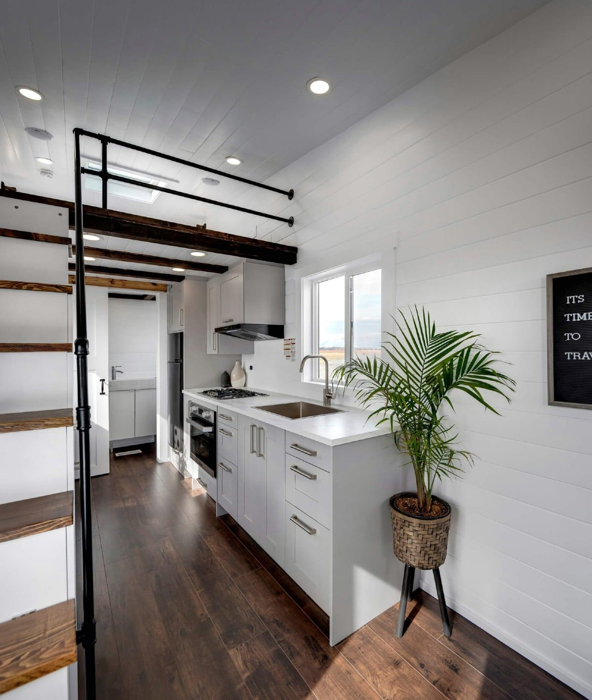Ladder to loft on left side of image with kitchen counter in background