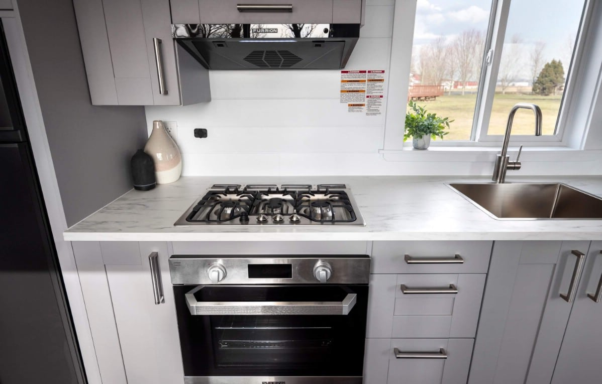 Full sized gas stove in tiny house kitchen with white cabinets