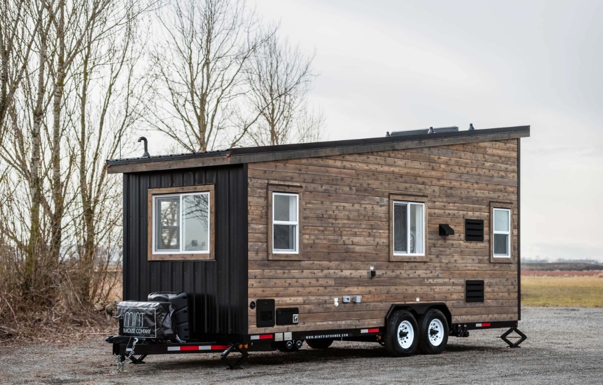 Tiny house with black and wood siding parked in lot