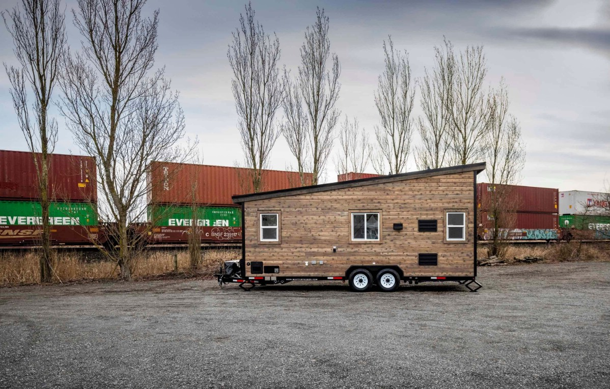 Tiny house with sloping roof and wood siding in parking lot