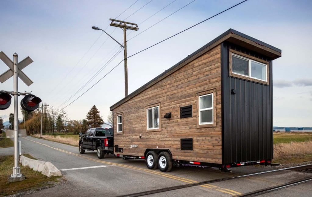 Tiny house with wood siding being pulled by truck