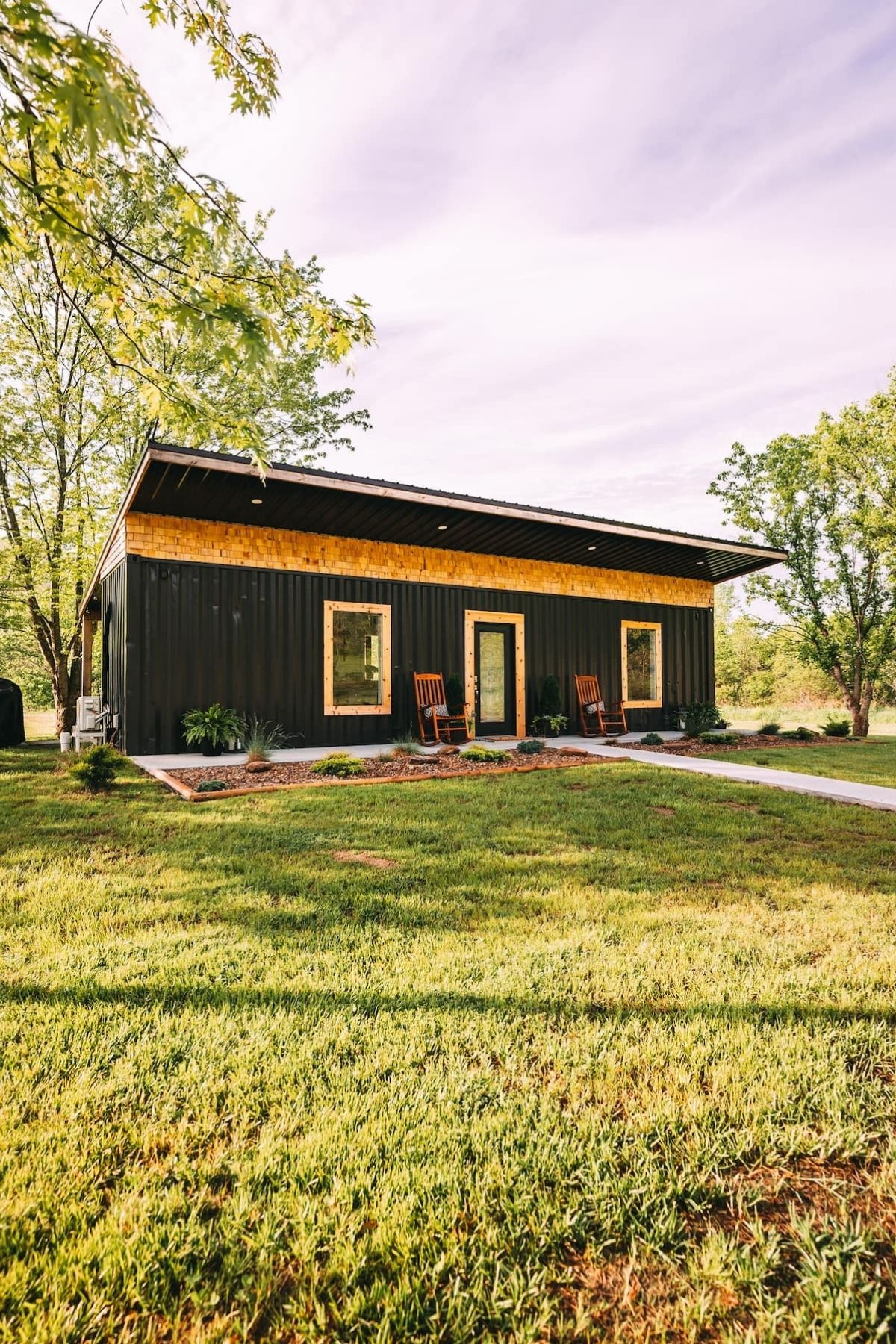 Black and wood tiny home on lot with trees in background