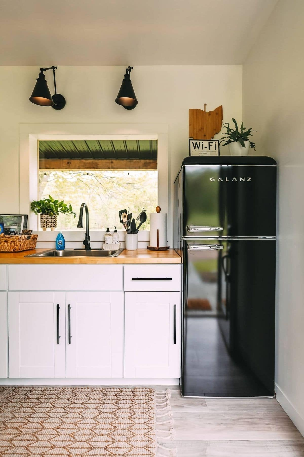 Apartment sized black refrigerator against wall next to white cabinets and sink