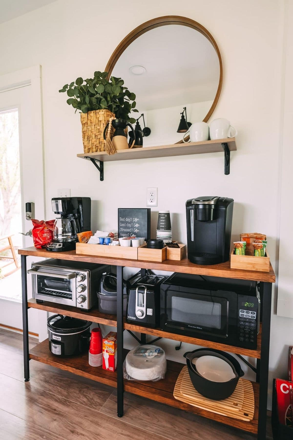 Wide black and wood shelf against white wall holding small kitchen appliances and supplies