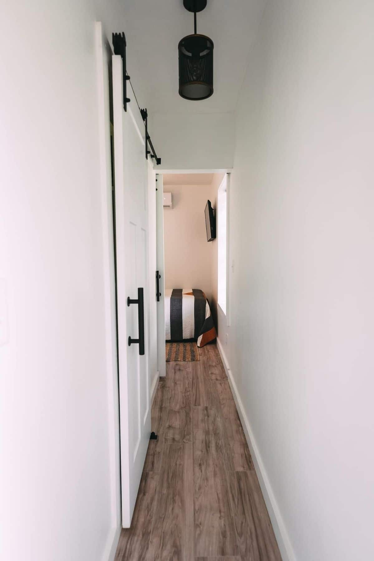 White narrow hallway leading to bedroom with dangling light in center