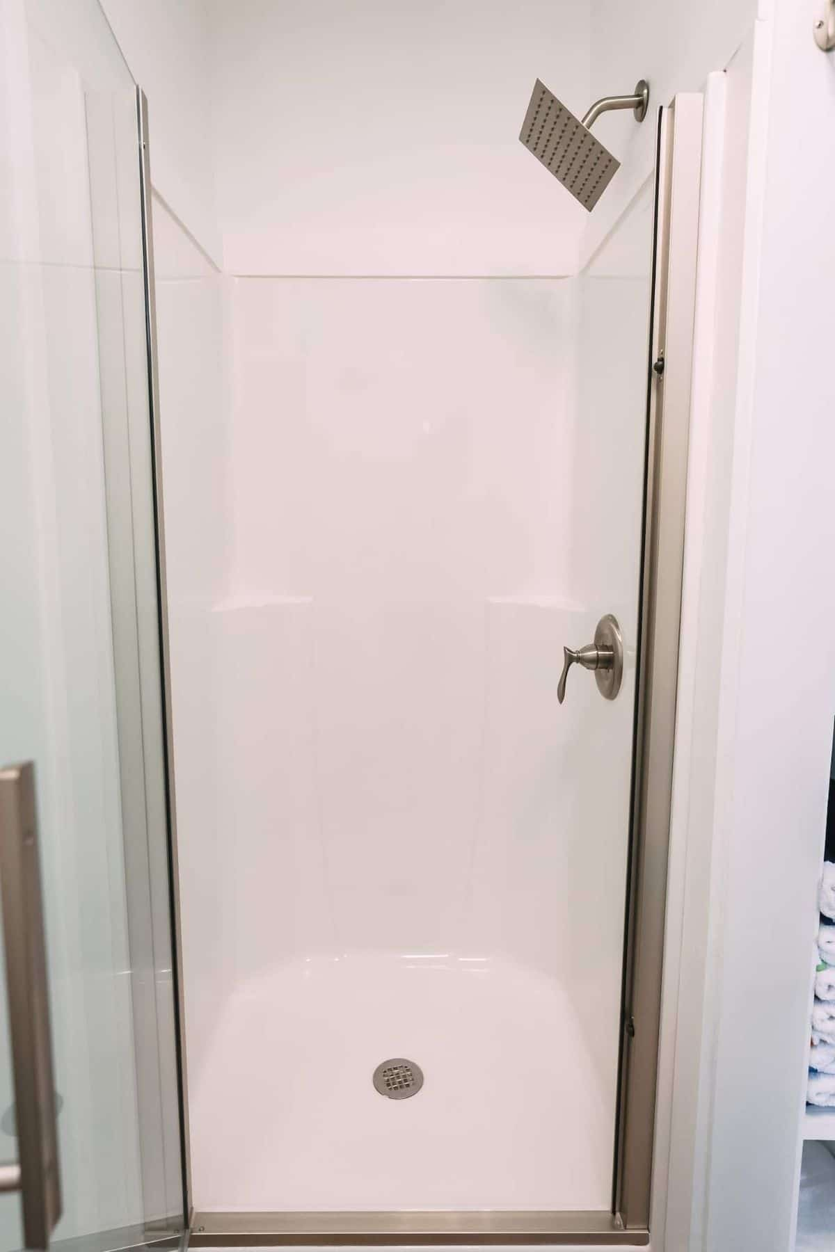 Small white shower stall with rainwater shower head