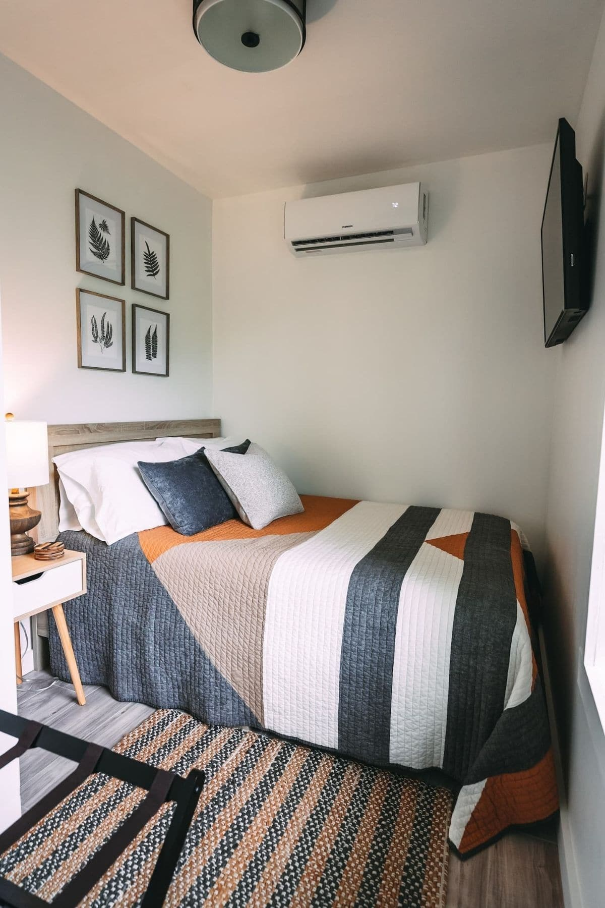 Striped bedding on bed against end of home in tiny bedroom
