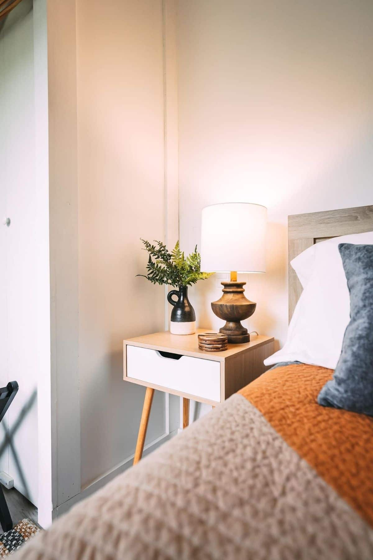 Small modern side table next to bed in tiny house bedroom with white walls