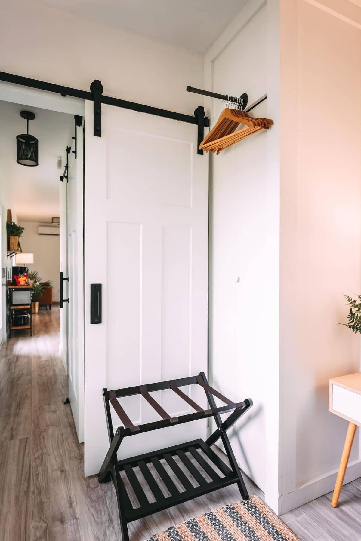 Barn door style bedroom door with rod and hangers at ceailing