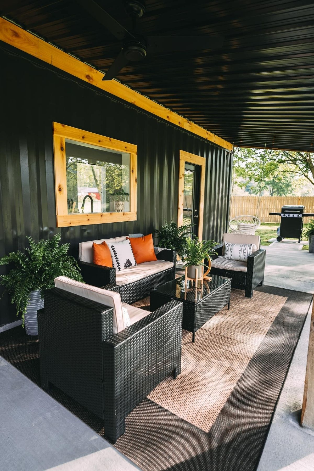 Black outdoor furniture set under awning by wood trimmed window