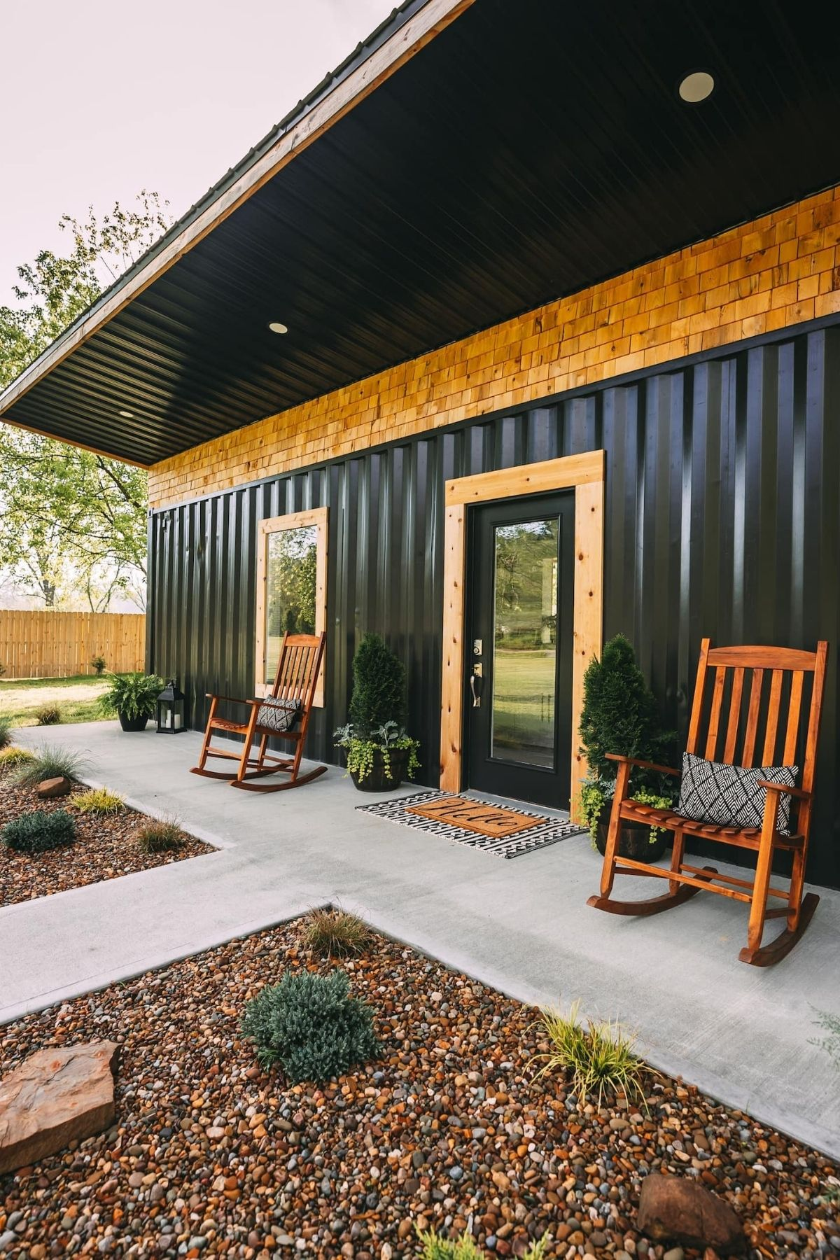 Wood trim around black front door to black shipping container home
