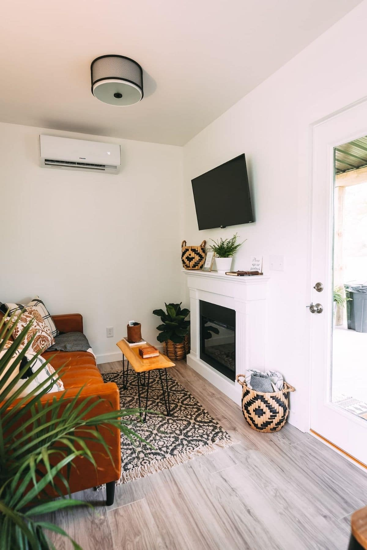 Tiny living area with white walls and fireplace below TV