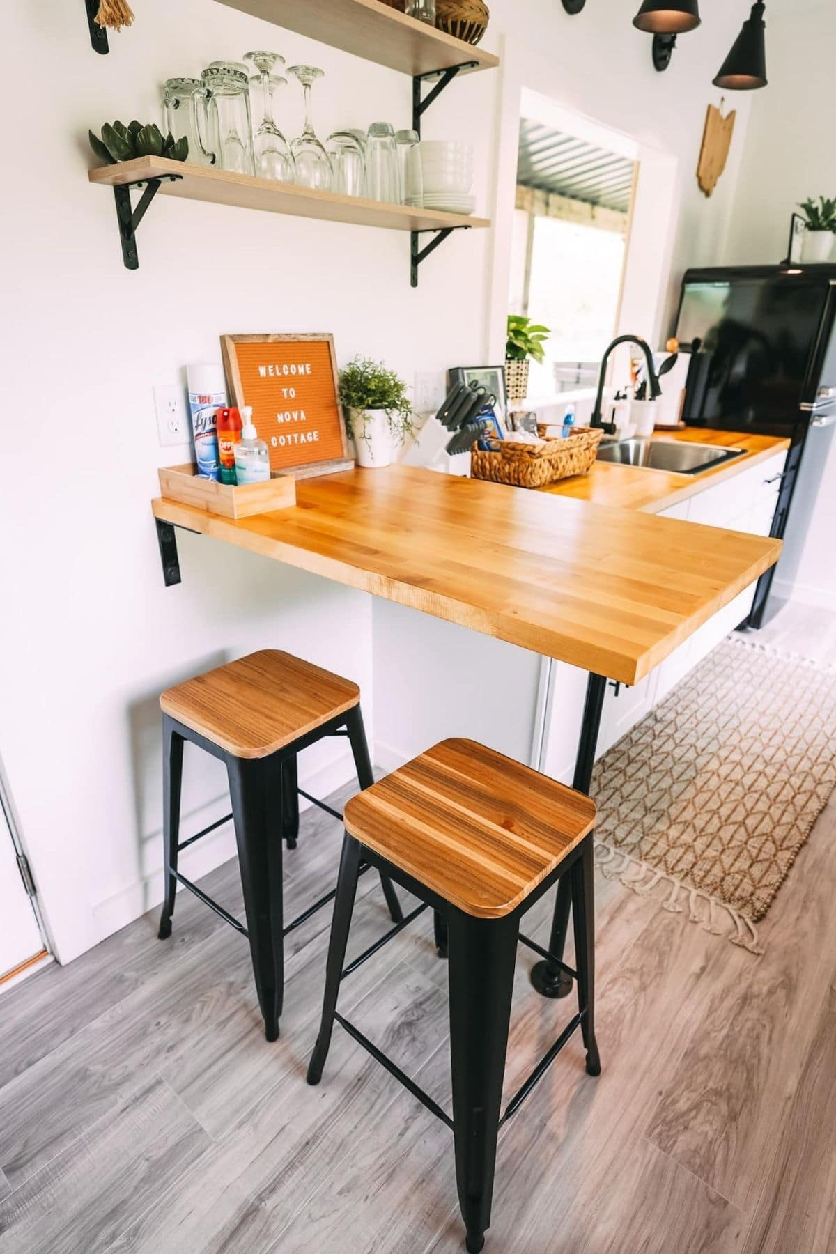 Butcher block bar at end of kitchen counter with wood and black stools