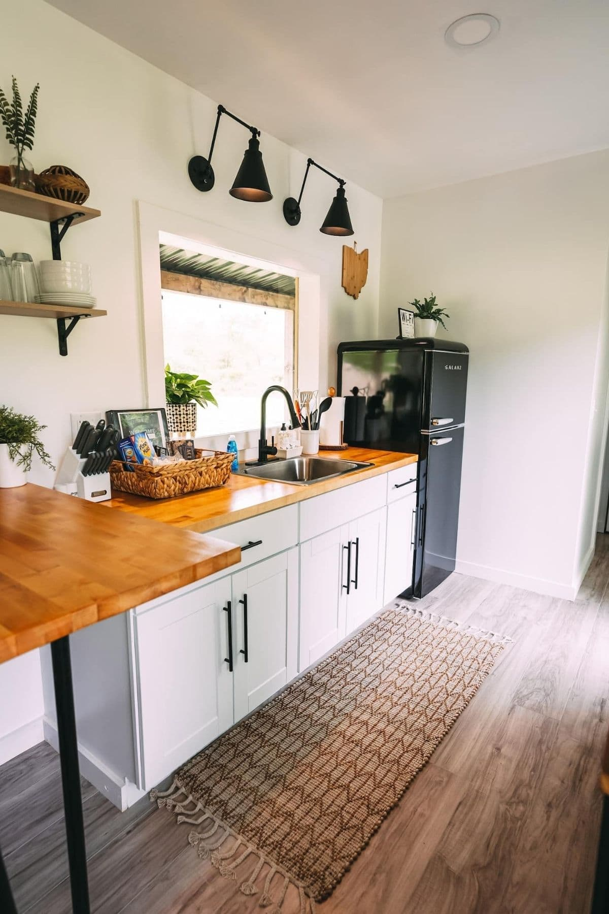 White cabinets with butcher block top against wall under large window