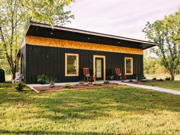 Black and wood converted shipping container home with rocking chairs on porch