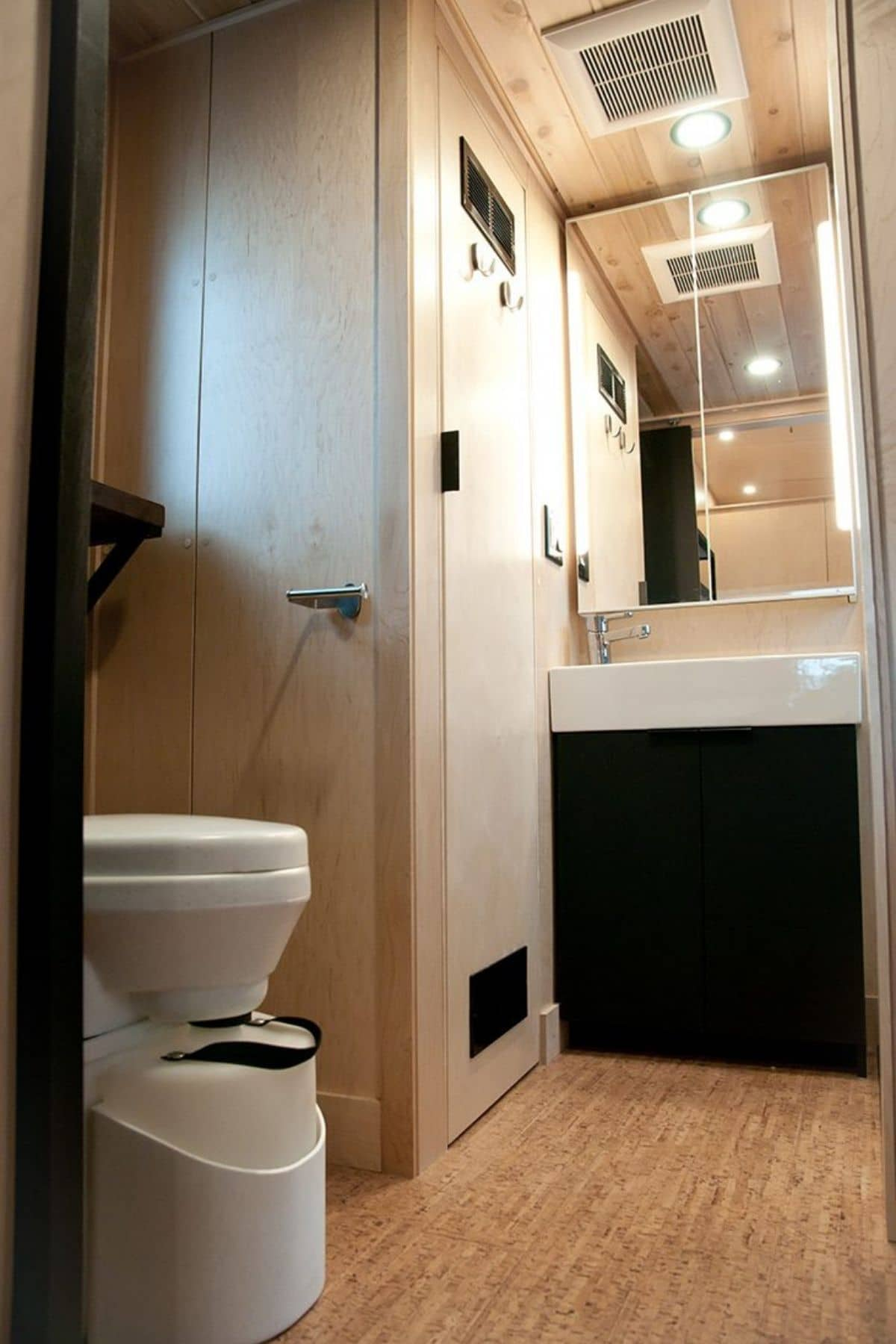 Compost toilet in foreground with closet and sink in background