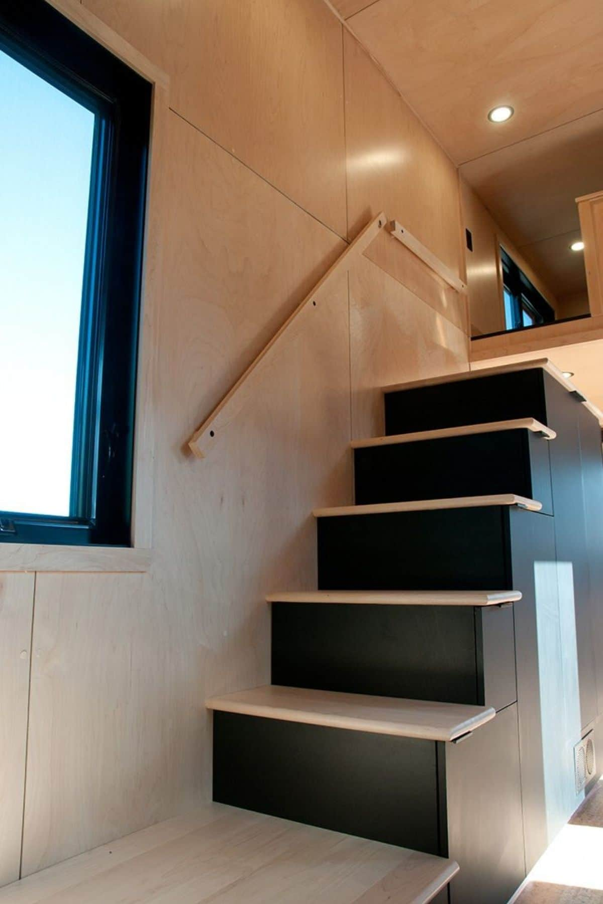 Black and natural wood stairs leading to loft
