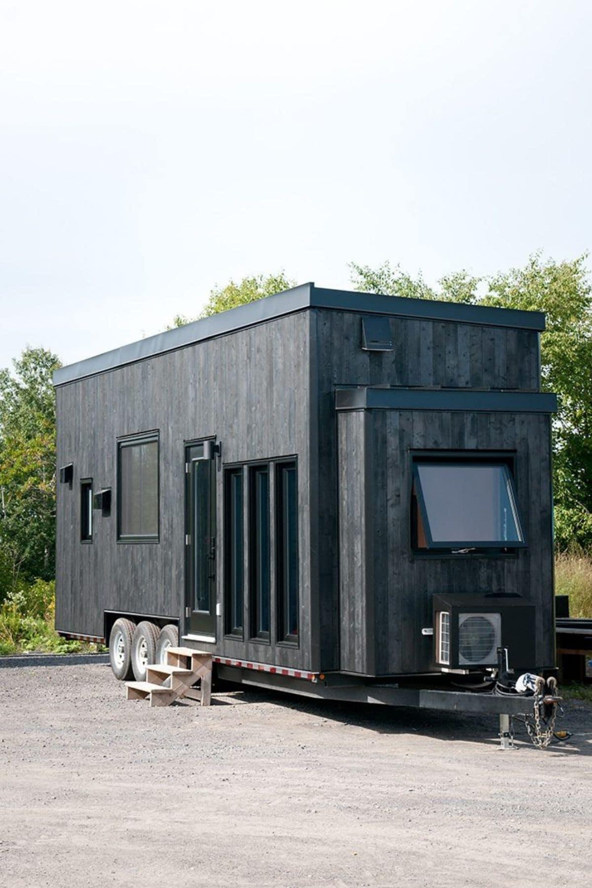 Dark gray siding on tiny home with three long windows on side