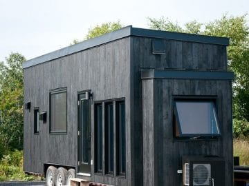 Black tiny home on lot with windows on side