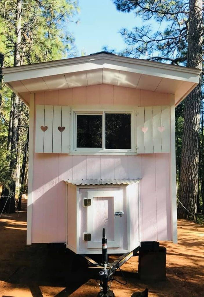 White shutters on end window of pink tiny home