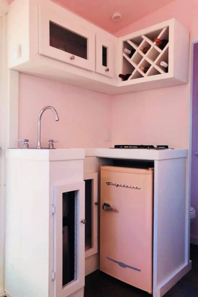 Corner of pink home with retro pink refrigerator under white cabinet
